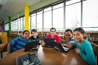 Group of five kids with laptops around a table smiling