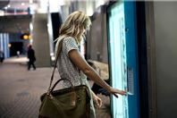 Woman with purse using digital vending machine