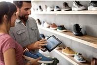 Retail assistant with tablet in shoe shop